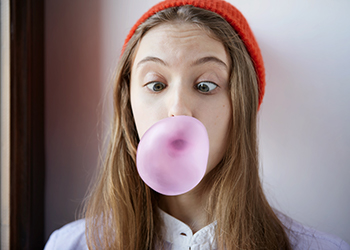 Teenager popping pink chewing gum
