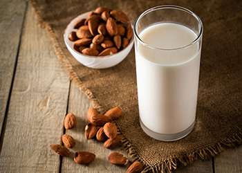Tall glass of almond milk, sitting next to a small bowl of almonds on a table
