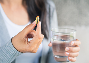 Woman holding a vitamin pill and a glass of water