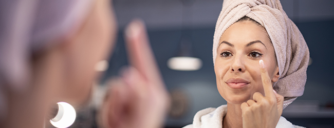Woman applying face cream in front of a mirror