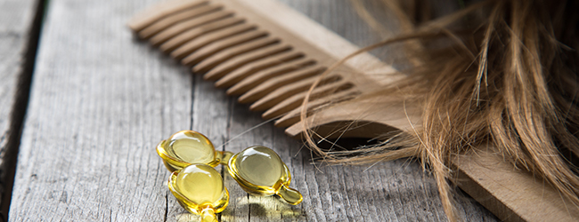 hair care oil, comb and hair in close up