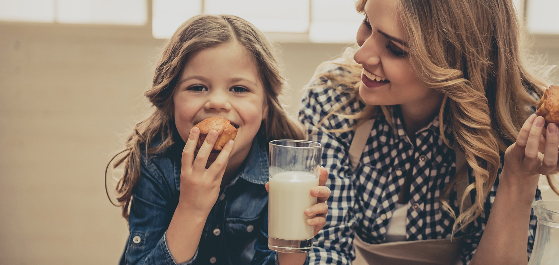 mother and daughter eating cookies and drinking milk