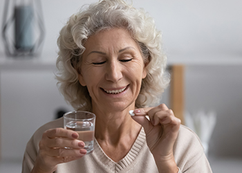 eldery woman sitting in bed and taking dietary supplement